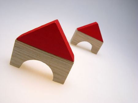 two wooden toy small houses on  light background,  close up photo