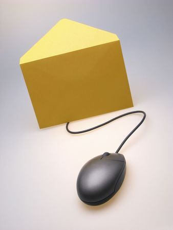 yellow envelope and  computer mouse on  light background,  close up photo