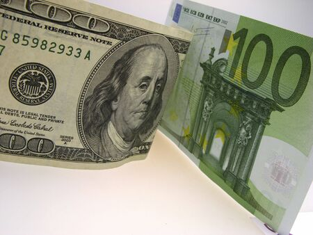 denominations: two paper denominations hundred dollars and hundred euros on  light background,  close up