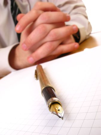 clasping: Young busimessman clasping his hands and pen, closeup