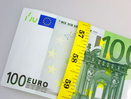 budget restrictions: Banknote hundred euros tied up in the meter,  close up, on  light background