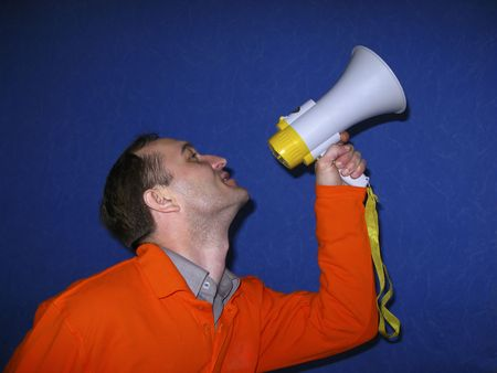 man in bright clothes with  loudspeaker in  hand shouts on  dark blue background Stock Photo - 2852827