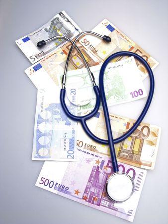 monetary: Medical stethoscope and monetary denominations of euro, close up