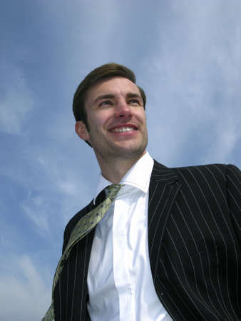 Portrait of  young businessman on  background of  sky photo