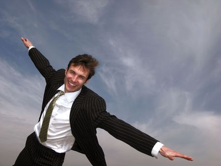 young businessman in good mood on  background of  sky