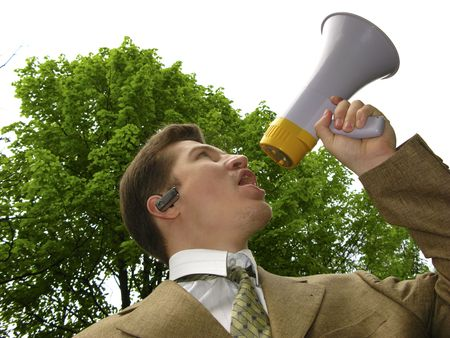 young businessman shouts in megaphone on  background of  green tree photo