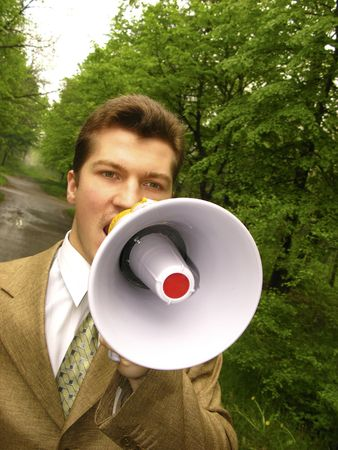 young businessman shouts in megaphone on  background of  green tree Stock Photo - 3020849