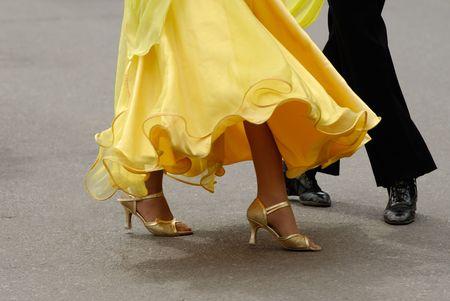 Legs of  dancing pair, shadow on asphalt Stock Photo