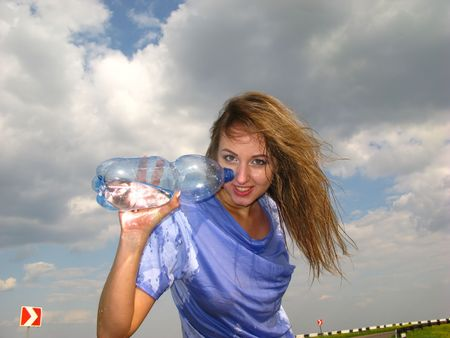 woman drinks water on  background of clouds photo
