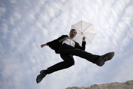 victorious: businessman jumps with  umbrella on  background of  blue sky with clouds Stock Photo