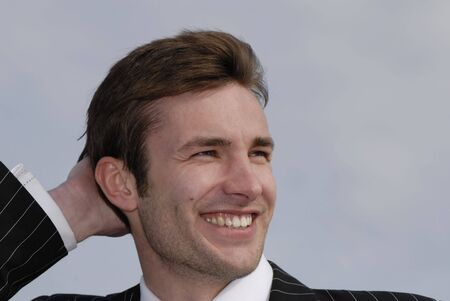 Portret van vrolijke, lachende jonge zakenman op de achtergrond van de hemel