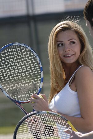 conducts: woman conducts conversation with young instructor on tennis on training