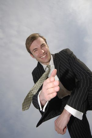 executive affable: young successful businessman submitsa hand for  greeting, on  background of  sky