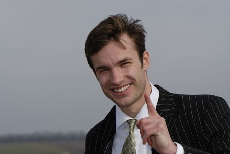 executive affable: young successful businessman gesticulates  finger