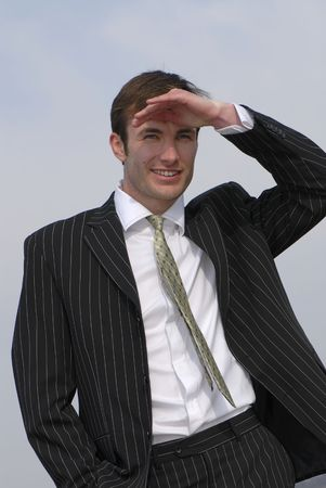 executive affable: young successful businessman looks in  distance on  background of  sky