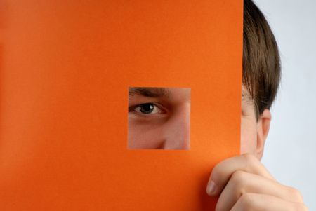 young businessman looks through an aperture in sheet of paper Stock Photo