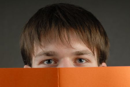 man looks through cover of book photo