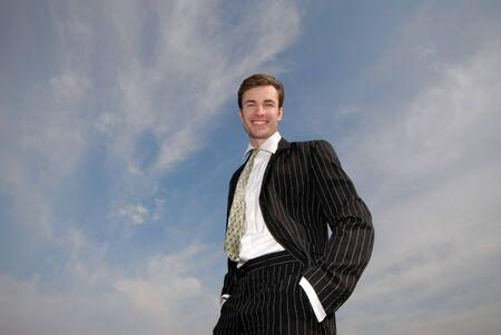 smiling businessman in  black business suit on  background of  blue sky photo