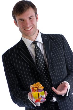 白い背景で隔離の手でギフト ビジネス スーツに笑みを浮かべて青年実業家 写真素材