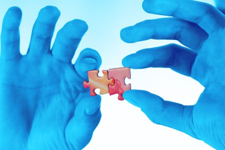 tonality: Mans hands hold game elements puzzle,  photo in  blue tonality Stock Photo
