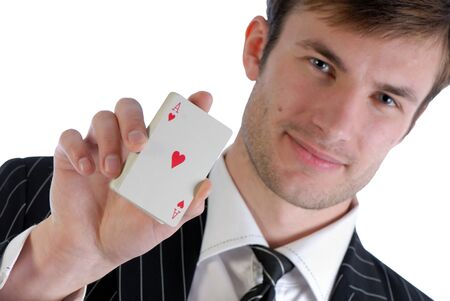 Young  man in  suit holds in  hand playing cards isolated on  white background photo