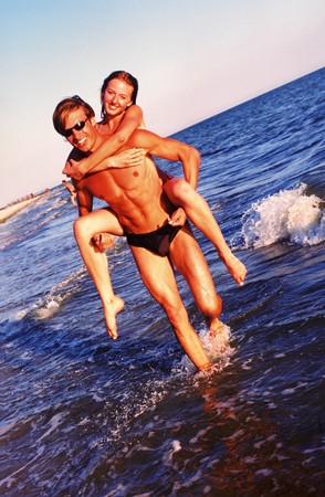 Pair young people in  sunny day on seacoast Standard-Bild