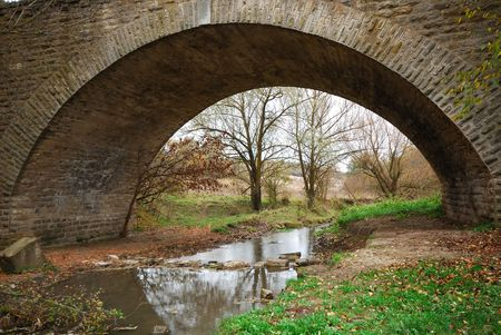 footplate: old stone bridge through small river, autumn Stock Photo