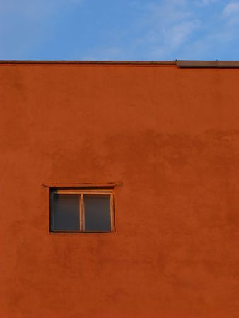 claret: single closed window on  background of  claret wall and  blue sky
