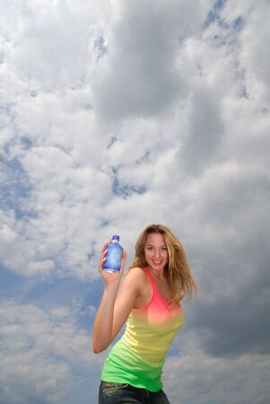 young nice woman holds in hand bottle of water on  background sky Stock Photo - 5028872