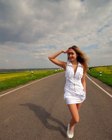 young nice woman goes on road, spring day Stock Photo - 5028871