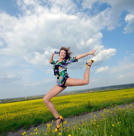young woman highly has jumped up above  field,  bright sunny day Stock Photo - 5028877