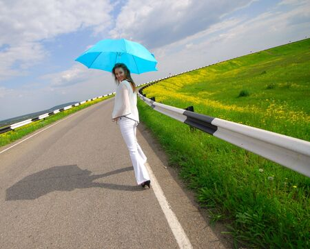 woman with  blue parasol goes on road in  bright sunny day photo