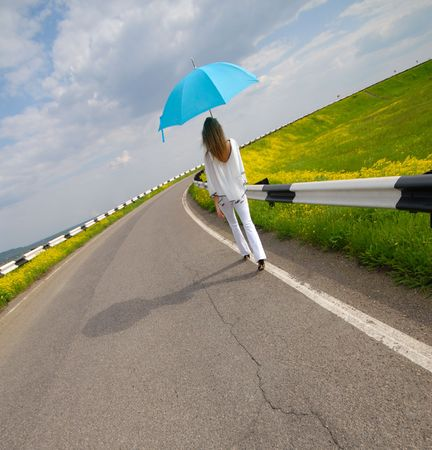 woman with  blue parasol goes on road in  bright sunny day Stock Photo - 5002476