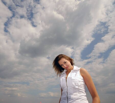 Portrait of  young nice woman in white clothes on  background of clouds  photo