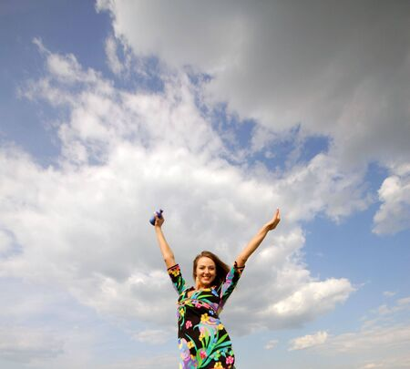 active young woman with  lifted hands on background of  sky with clouds photo