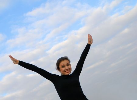lifted hands: young nice woman with  lifted hands on  background of  blue sky