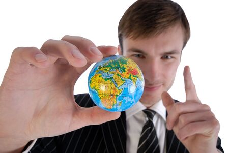 young businessman in  business suit holds model of globe in  hand and reflects photo