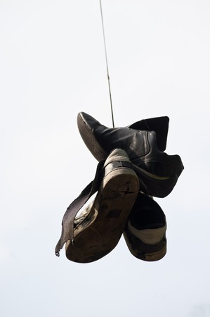 old, torn  up sporting trainers  entangled by a lace on a light background photo