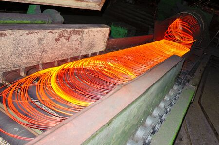 out of production: metallurgical production , a burning hot metal is stretched out through rollers Stock Photo