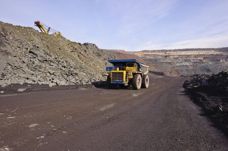 The big diesel lorry takes out iron ore from an open-cast mine photo
