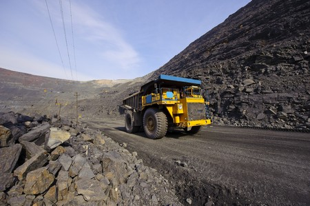 The big diesel lorry takes out iron ore from an open-cast mine