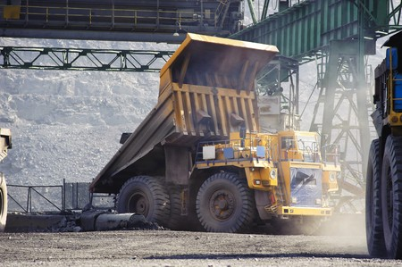 The truck  ore in the crusher bunker, an open-cast mine on extraction of iron ore by open way photo