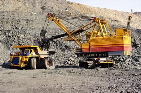 読み込み、浚渫機および貨物自動車によるオープンな方法でキャリアの鉄鉱石の輸出 写真素材