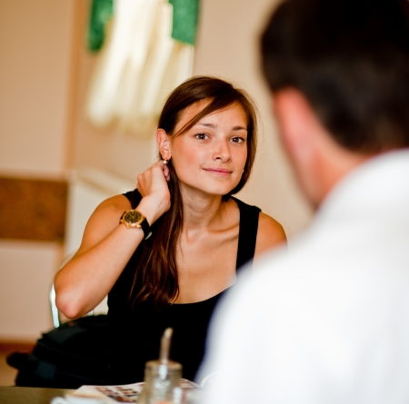 beautiful young woman speaks with the man in cafe and does up hair