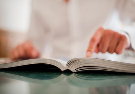 lezing: De zakenman wijst een vinger in het boek op een lichte achtergrond dim Stockfoto