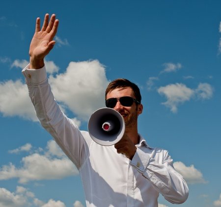 bespectacled man: nice young businessman shouts in a megaphone against the blue sky with clouds Stock Photo
