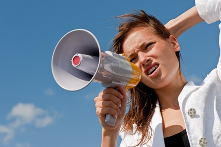 nice young businessman shouts in a megaphone against the blue sky with clouds Stock Photo - 8667803