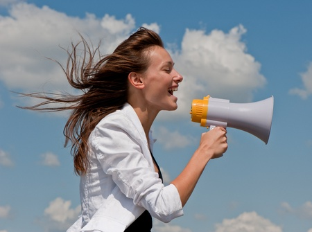 nice young businessman shouts in a megaphone against the blue sky with clouds Stock Photo - 8667802