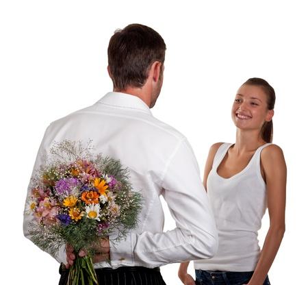 女の子は、白い背景で隔離する予定で背中の後ろに花の束を持つ男