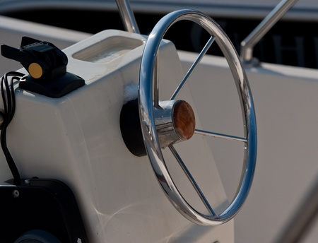 Steering wheel of a sea boat in a sunny day photo